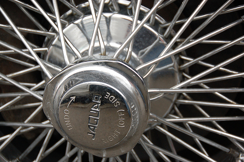 "Old Jaguar E-type sports car: hubcap sprocket text ""UNDO –> RIGHT (OFF) SIDE"""